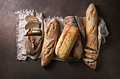 Variety of loafs fresh baked artisan rye, white and whole grain bread on linen cloth over dark brown texture background