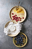 Fresh homemade cottage cheese in cheesecloth served in ceramic bowl with blueberries, raspberries and honeycombs