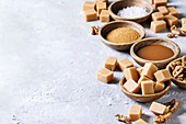 Salted caramel fudge candy served with fleur de sel, caramel sauce, brown cane sugar and caramelized walnuts in wood bowls