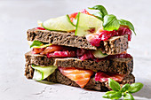 Sliced beetroot marinated salmon sandwiches with rye bread, cucumber, basil and lemon served in stack on wooden cutting board