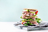Beef and vegetables sandwiches with sliced meat, cucumber, green salad, rye whole grain bread in stack on wooden tray