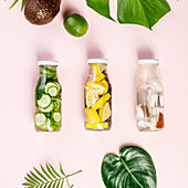Detox fruit infused water, tropical fruits and leaves on pink pastel background