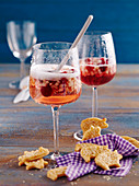 Glasses of fruity New Year's Eve punch with Prosecco and cranberries with spicy pig-shaped biscuits