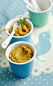 Baby food made with vegetables and beef in small cups with spoons