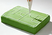 A football pitch cake being decorated