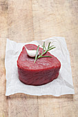 A raw fillet of beef with garlic and rosemary