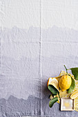 Lemons with leaves on a purple tablecloth