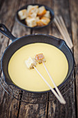 Cheese fondue with white bread in a cast iron pan