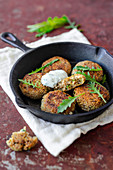 Quinoa croquettes with herb quark in a cast iron pan