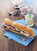 A baguette sandwich with ham, chive cream and meat salad in a jar