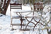 Kleine Sitzgruppe im verschneiten Garten