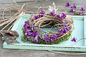 Kranz aus Moos, Gras und Rinde mit Blüten-Girlande