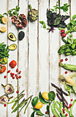 Colorful vegetables and greens on white table background