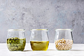 Glass jars with traditional Basil pesto sauce, olive oil, pine nuts on kitchen table with white linen tablecloth