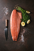 Whole raw uncooked salmon fillet server with green dill, lemon, salt, pepper, chef s knife over dark brown texture background