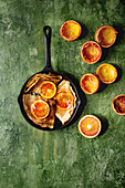 Homemade crepes pancakes served in cast-iron pan with bloody oranges and rosemary syrup with sliced sicilian red oranges over green texture background
