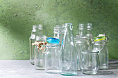 Variety of different shape empty opened glass bottles with and without lids standing on grey table with green wall as background