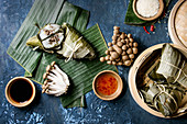 Asian rice piramidal steamed dumplings from rice tapioca flour with meat filling in banana leaves served in bamboo steamer. Ingredients and sauces above over blue texture background