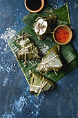 Asian rice piramidal steamed dumplings from rice tapioca flour with meat filling in banana leaves