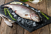 fresh trout with rosemary, lemon and ice on slate on wooden table