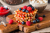 Belgian waffles with fresh berries and coffee on cutting board on rustic wooden background