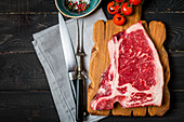 Raw fresh meat Club Steak, seasoning and meat fork and knife on dark wooden background