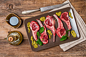 Raw fresh lamb ribs with sauce on plate on wooden background, top view