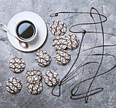Cookies in white glaze and cup of hot coffee on old gray background. Top view