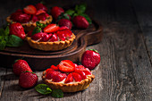 Fresh homemade strawberries tarts on wooden background