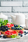Fresh homemade berrie tarts with blueberries, blackberry and strawberries on gray background