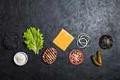 Zutaten für schwarzen Burger: gegrillte Hähnchenfrikadelle, Brötchen, Zwiebel, Tomate, Kopfsalat, Essiggurken, Sauce und Toastkäse