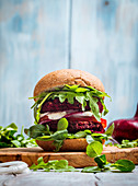 Vegetarian burger made of beetroot, tomato, corn salad and arugula on wooden background