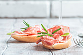 Concept of italian food with bruschetta with prosciutto on white background