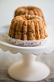 Two mini coffee cakes with almonds on a cake stand