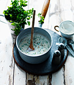 Parsley sauce with salt and pepper in a saucepan