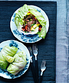 Iceberg salad rolls with pork, mango, tomatoes and peppers