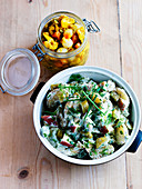 Potato salad with apple and herbs, and a jar of piccalilli