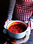 A woman serving a saucepan of tomato sauce