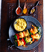 Raw chicken kebabs with marinade, zucchini, peppers and spices