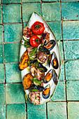 Grillplatte mit Schweinespiessen, Muscheln und Gemüse