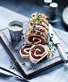 Turkey roulade filled with herbs, tomatoes and cheese, sliced