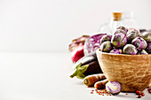 Purple Brussels sprouts in a bowl and healthy ingredients on concrete background