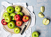 Green cooking apples and red eating apples with a knife on a round wooden board