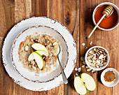 A bowl of organic oatmeal porridge with sliced apple on top and bowls of flaked almonds and cinnamon
