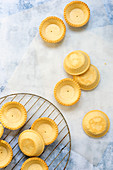 Small baked pastry tartlet cases cooling on a wire rack and baking paper