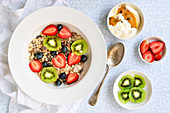 A bowl of muesli with strawberries, kiwifruit, blueberries and passionfruit yogurt