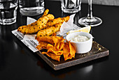 Fish and Chips mit Dip auf Holzbrett