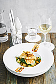 Delicious dish with cod, roasted potatoes and herbs served on table with cutlery and wine