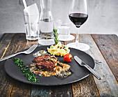 Steak mit Pilzsauce und Polenta serviert mit Wasser und Rotwein
