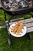 High angle view of plate of grilled shrimp on skewers cooling by the side of the barbecue